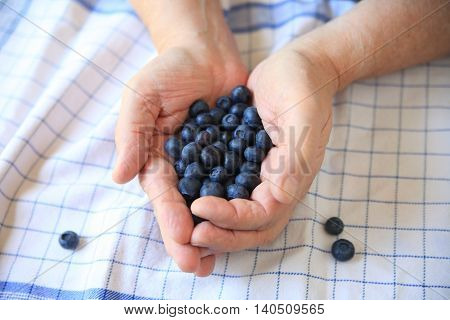 A man holds blueberries in both his hands over a dish towel.