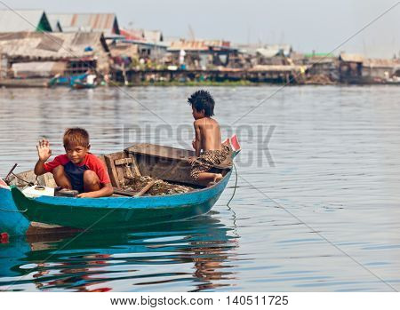 SIEM REAP, CAMBODIA-NOVEMBER 17, 2011: An unidentified boys on a boat floating on Tonle Sap lake in Siem Reap. Tonle Sap is the largest lake in SE Asia peaking at 16kkm2