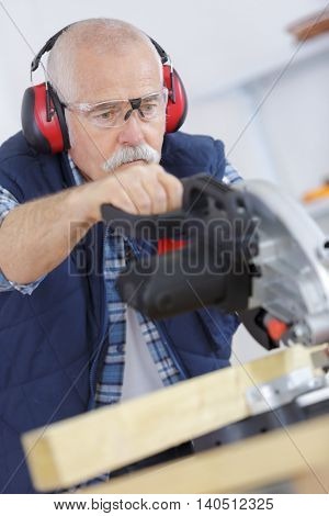 senior carpenter cutting wooden plank with circular saw