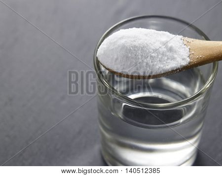baking soda on top of glass of water on the black background