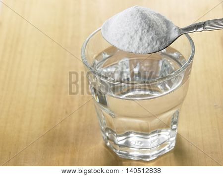 pouring baking soda to glass of water on the wooden background