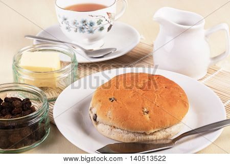 Tea with a traditional British teacake of raisins sultanas and spices