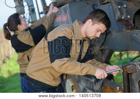 young worker checks the pressure of the engine