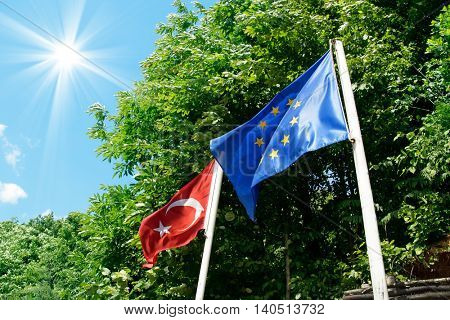 Turkish and European Union flag over sunny sky.