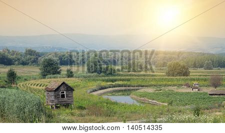 Rural landscape of old log cabin beside small river and fields in plains