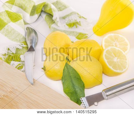 Juicy lemons silicon squeezer knife Zester and wooden cutting board on the table.