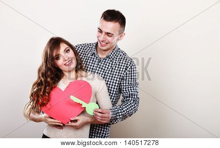 Smiling young couple holding paper key to heart sign love symbol. Loving husband and wife dreaming about new home.