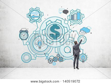 Man in suit is drawing startup sketch on concrete wall. Gears light bulb arrows chart dialogue icons surround dollar sign in center. Concept of successful startup.