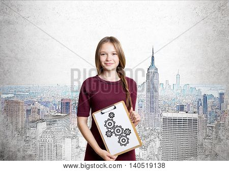 Young lady is standing in red dress with braided hair and holding clipboard with gears sketch on it. Background is painting of New York. Concept of strategy importance in business