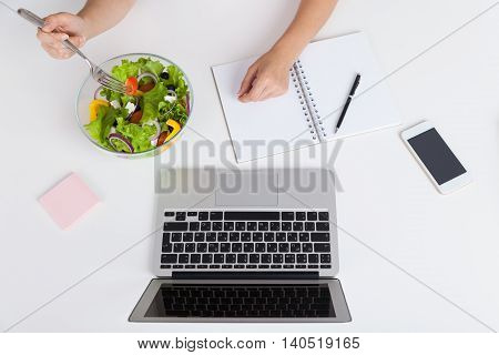 Woman eating her lunch in office. Bowl of vegetable salad laptop cell phone and notebook on table. Concept of lunch break at busy office and healthy food. Top view