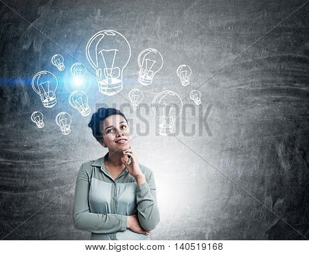 Woman in shirt is standing in front of chalboard with light bulb sketches on it thinking about new way to solve difficult problem. Concept of original idea in business. Toned image