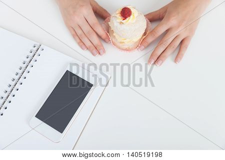 Woman hand holding cupcake. Her smart phone lies on top of notebook on table. Concept of tasty cupcake eating during lunch break and difficulties of dieting. Close up. Top view