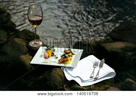 Picnic near water decorated fish meal with lemon glass of wine served food