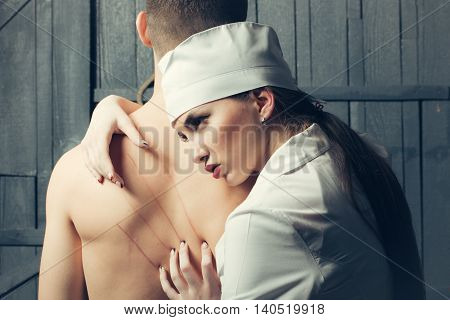 Sexy young couple of pretty nurse in white uniform with fingers on undressed male back