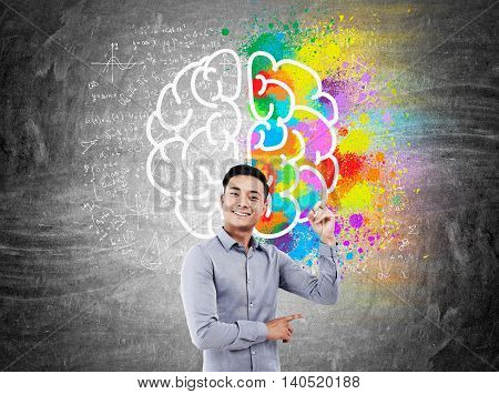 Businessman in shirt standing in front of chalkboard with colorful brain sketch and equations pictured on it pointing upwards and smiling broadly. Concept of finding new thing in science.