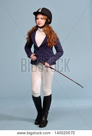 redhead girl with freckles in riding clothes and helmet on a light background the concept of a jockey