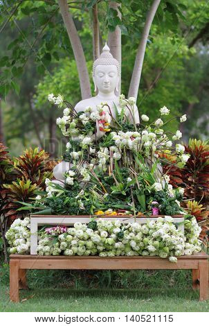 Buddhism worship with offering flowers and garland to buddha statue on Magha Puja Asalha Puja and Visakha Puja Day in Thailand