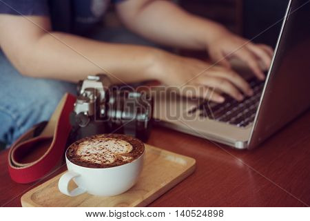 Businesswoman Is Working With Laptop, Holding A Coffee In Coffe Shop