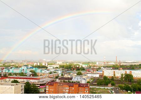 Rainbow over industrial sity. Rooftop view on railroad station of Omsk, Russia