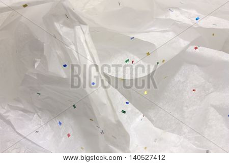 This is a photograph of White tissue wrapping paper with confetti design background