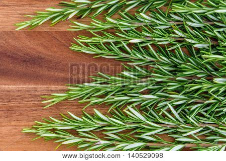 Sprigs of rosemary lined up horizontally on a wood cutting board