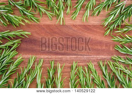 Sprigs of rosemary lined up in a circle on a wood cutting board