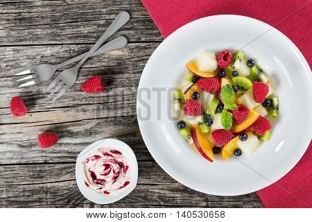 delicious fruit and berry summer salad decorated with mint leaves in white wide rim dish with dessert forks on wooden boards and cream sauce bilberry dip view from above