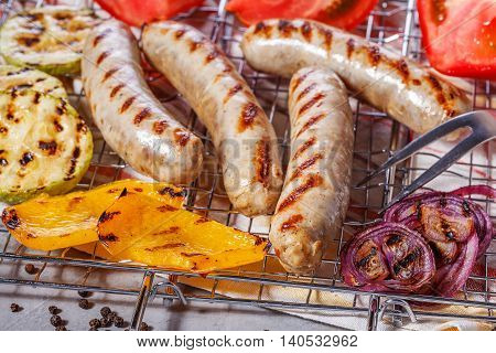 Cooked sausages with vegetables and spices on the grill grate.