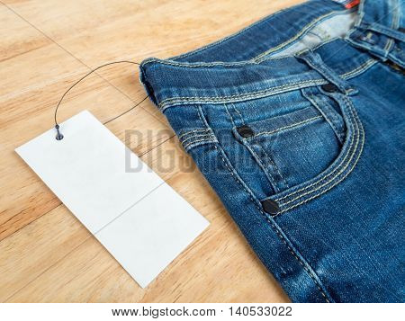 Close-up of blue jeans with deerskin label and white blank price tag on wooden texture background