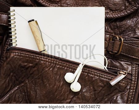 Notebook, pen and headphone on a leather bag.