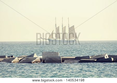 three mast yacht in clear blue sea taken over concrete breakwater structure