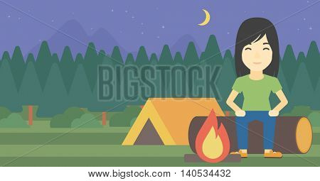 An asian woman sitting on a log near a fire on a background of camping site with tent. Woman sitting near a campfire at a campsite. Vector flat design illustration. Horizontal layout.
