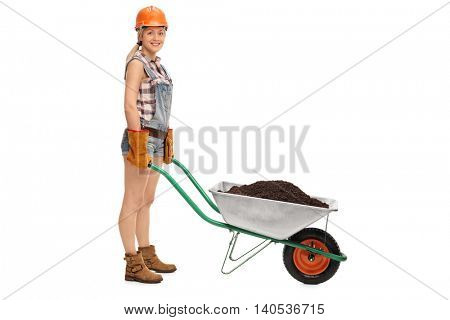 Young female worker posing with a pushcart full of dirt isolated on white background