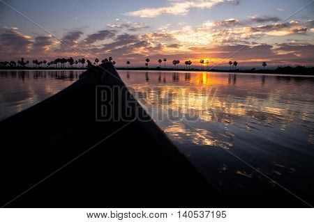 Kayak sailing on Rio Negro at sunrise. The sun rising behind clouds creates bautiful reflections on the river in Paraguay's Pantanal