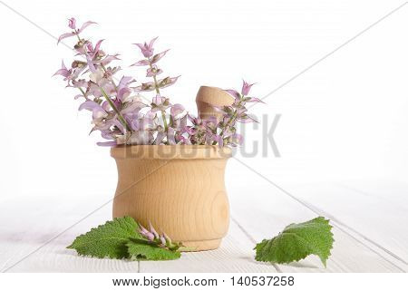 Fresh sage in a mortar on an white wooden table