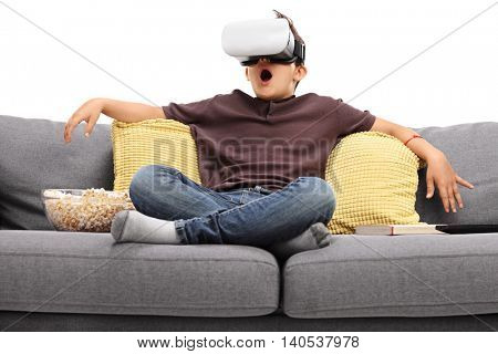 Astounded little kid using virtual reality goggles seated on a sofa isolated on white background