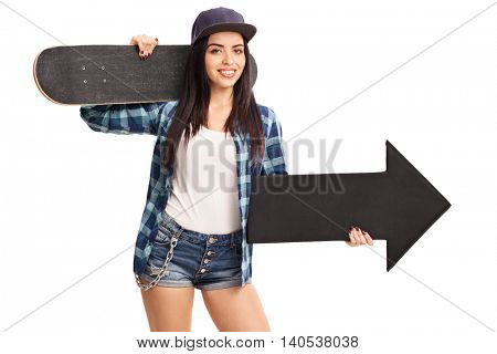 Joyful female skater holding a skateboard and a black arrow pointing right isolated on white background