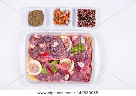 Steaks of red meat marinated with emulsion of lemon juice and olive oil and seasoned with pepper of various colors fresh thyme and parsley hot pepper garlic and finally Barolo or a high good red wine