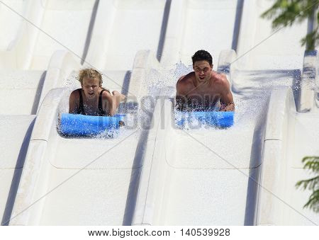 Rhodes Greek-July 03 2016:Two young people on the mat racer slide in Water park.Mat racer slide is very popular for young people in the Water Park.Water Water Park is located  on the island of Rhodes in Greece and one of the most largest in
