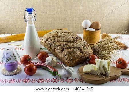Homemade Bread, Milk, Barley Ears, Homemade Salty Cheese On A Wooden Board, Garlic, Peppers, Tomatoe