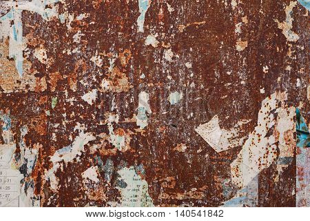 grunge ripped poster on rusty iron sheet background - texture of torn advertisement on an old rusty billboard panel