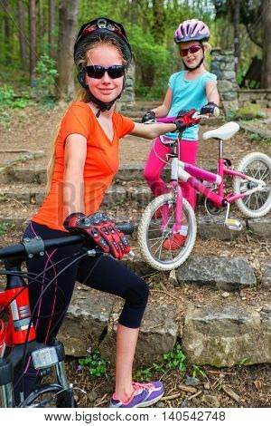 Bikes cycling family. Happy very young mother and daughter wearing bicycle helmet are cycling on bicycles into forest. Stairs in park.