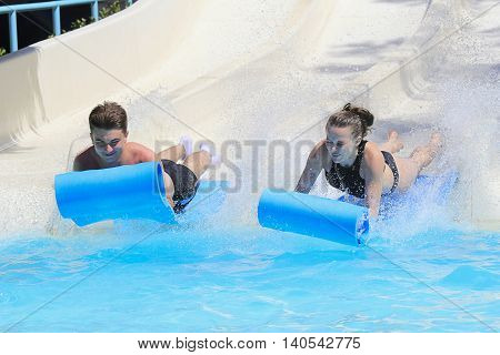 Rhodes Greek-July 7 2016:Two young people on the mat racer slide in Water park.Mat racer slide is very popular for young people in the Water Park.Water Water Park is located  on the island of Rhodes in Greece and one of the most largest in Europe