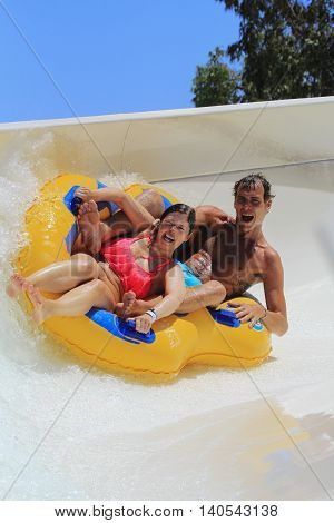 Rhodes  Greece-July 7 2016: Couple drive with tube on the rafting slide in the Water park.Rafting slide is one of many popular game for adults and children in park.Water Water Park is located  on the island of Rhodes in Greece and one of the most largest