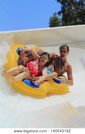 Rhodes Greece-July 7 2016;Couple drive with tube on the rafting slide in the Water park.Rafting slide is one of many popular game for adults and children in park.Water Water Park is located on the island of Rhodes in Greece and one of the largest in Europ