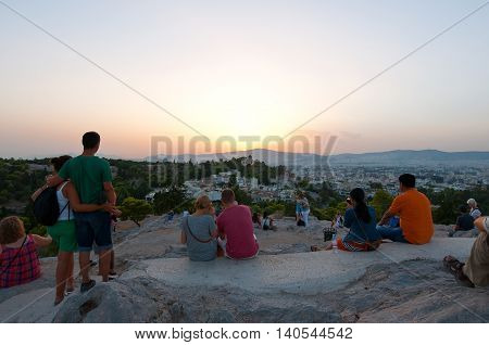 ATHENS-AUGUST 22: Tourists enjoy sunset from Areopagus hill on August 22 2014 in Athens Greece. Areopagus hill is located just bellow the entrance of the Acropolis.