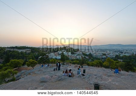 ATHENS-AUGUST 22: Tourists enjoy sunset from Areopagus hill on August 22 2014 in Athens Greece. Areopagus hill is located just bellow the entrance of the Acropolis. Athens Greece.
