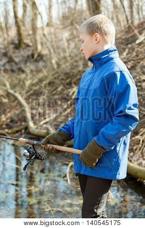 Blond Boy In Blue Jacket And Gloves Fishing