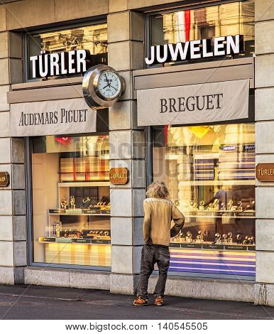 Zurich, Switzerland - 30 July, 2016: a person who looks as if being homeless is looking at the window of a store offering luxurious watches on Bahnhofstrasse street, which is Zurich's main downtown street and one of the world's most expensive shopping ave