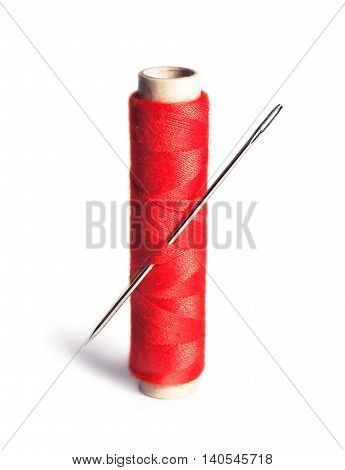 Sewing material, isolated on White background. Red thread and needle.